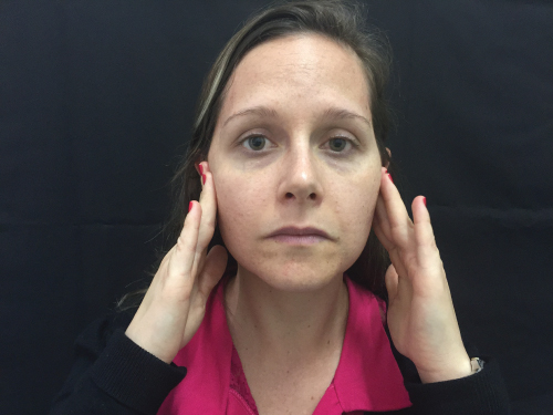 Photo showing a female Patient pointing to the principal area of her facial pain.