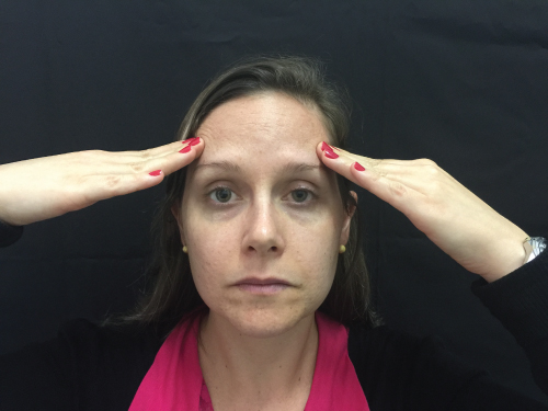 Photo showing a female Patient pointing to the principal area of her headache.